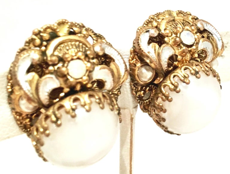 Mid-20th Century Miriam Haskell Style Vermeil Gold & Silver, Molded Glass, Faux Pearl Earrings. These Art Nouveau style earrings feature a central white opaque polished molded glass central stone with dog tooth prong set detail. Finely crafted and