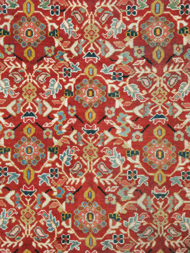 A vintage Persian Mahal carpet from the mid-20th century. There are eight offset rows of colorful rosettes with double leaf brackets in blue, green, yellow, and pink on a brick red field. The light brown main border is patterned with multicolored