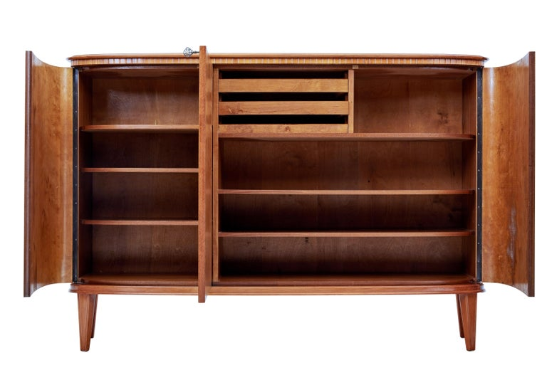 Striking 3-door sideboard, circa 1960.  Double door cupboard opens to reveal a partially fitted interior of 3-slide drawers and 3-shelves. Single door cupboard containing 3-shelves.  Matched flame mahogany used on the shaped doors with satinwood