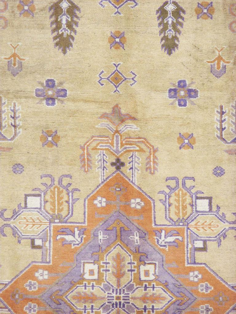 A vintage Turkish Oushak carpet from the mid-20th century. This unusual western Turkish Oushak is delineated in the Persian Heriz manner with a stepped soft orange pendant medallion on a camel-beige ground accented with floating vegetal motives