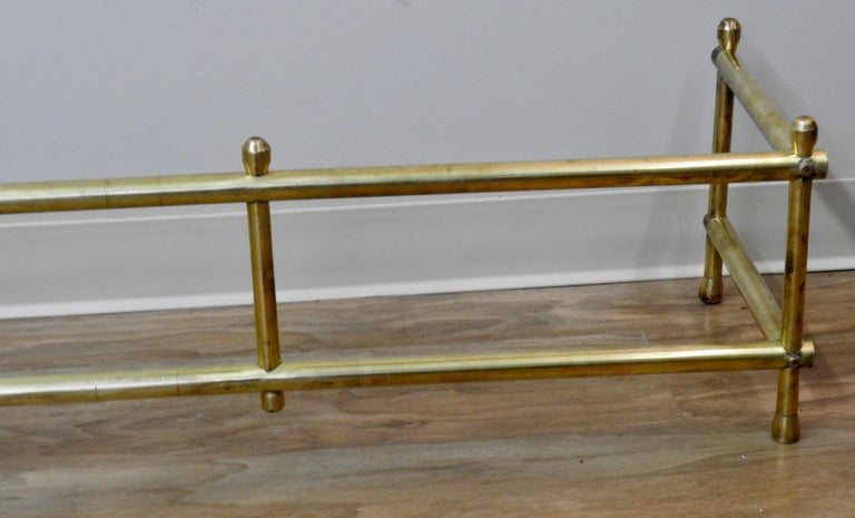 This beautiful 20th century solid brass fireplace surround is simple. Clean lines with a statement. It starts on a small tapered bun foot. Going up in simple vertical and horizontal lines capped with the same top as the feet.