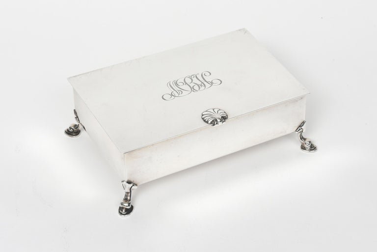 Tiffany & Co. rectangular sterling silver cigarette box rests on four inverted cabriole feet. Top of the box features a seashell detail handle and is initialed