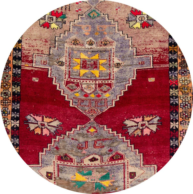 A hand knotted vintage Azeri runner with an artistic design on a red field, and multi-color accents throughout the piece. This rug measures 5'3