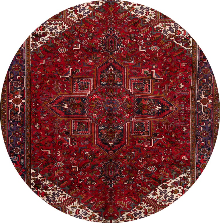 "A 20th century vintage Heriz rug with a red field, border and a central geometric medallion design. This hand knotted wool rug measures 9'3"" x 12'4""."