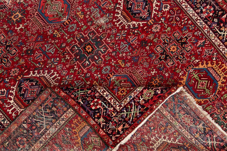 A beautiful vintage Heriz rug with a bright red all-over field and multicolored accents throughout the design.  This rug measures: 8'05