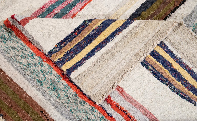 Beautiful hand knotted wool vintage Kilim rug. This rug has an ivory field with multicolored stripes, circa 1960
