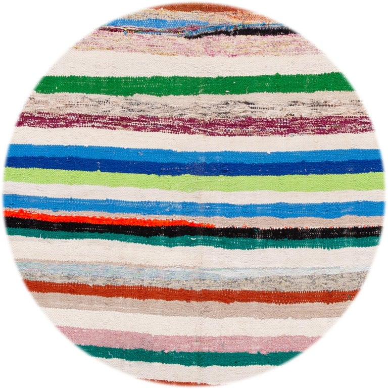 Beautiful hand knotted wool vintage Kilim rug. This rug has an ivory field with multicolored stripes, circa 1960.   This rug measures: 5'4