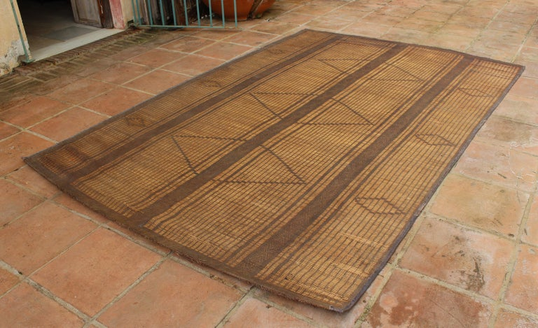 Moroccan Tuareg leather mats are made of dwarf palm tree fibers and hand woven with leather stripes, this are great to use indoor or outdoor, beautiful brown earth-tone colors. This vintage midcentury carpets are made in the desert of Morocco near