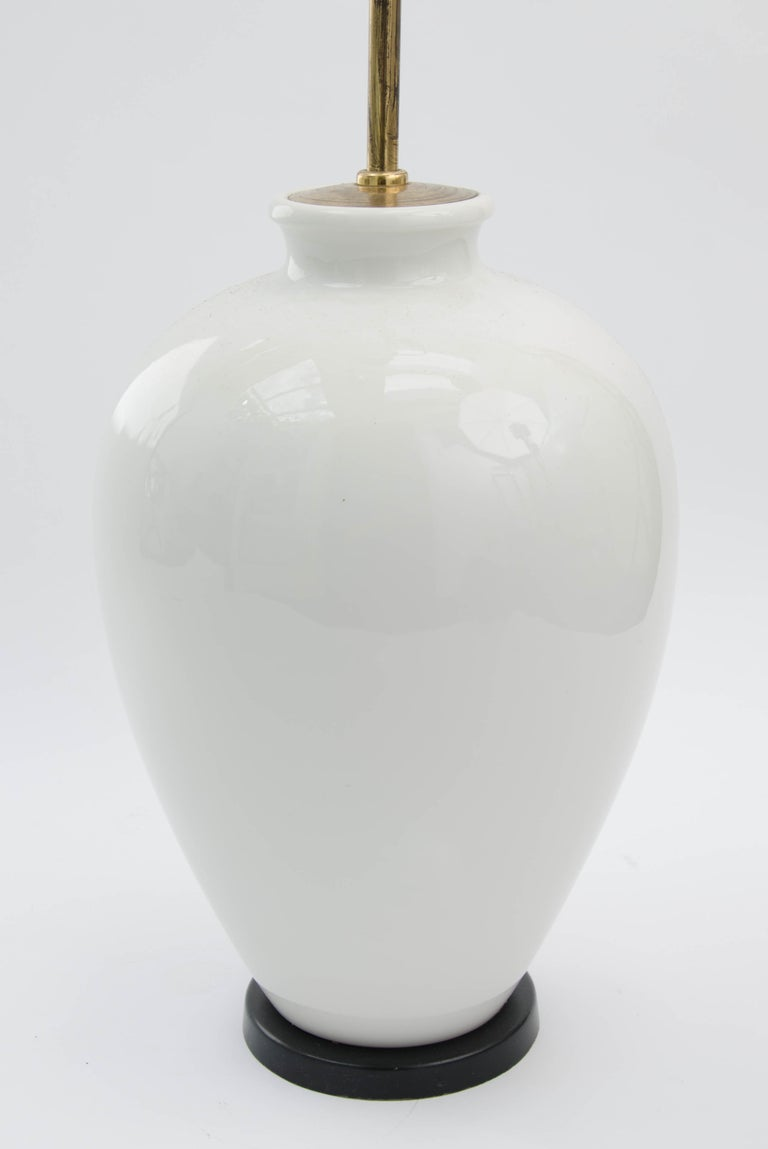 *** Please contact us for availability of this item. ***  White porcelain lamp by KPM of Berlin, Germany.  White porcelain body with brass stem and finial fitting, and black base. This is a tall, elegant piece which would work as a floor or table