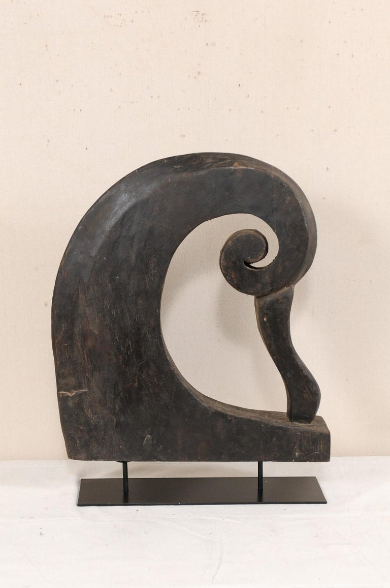 A South Indian (Kerala) wooden boat prow from the mid-20th century, with custom stand. This vintage hand carved boat prow from Kerala is adorn with pierced curling volute, reminiscent of a curling wave. It is supported upon a custom black iron