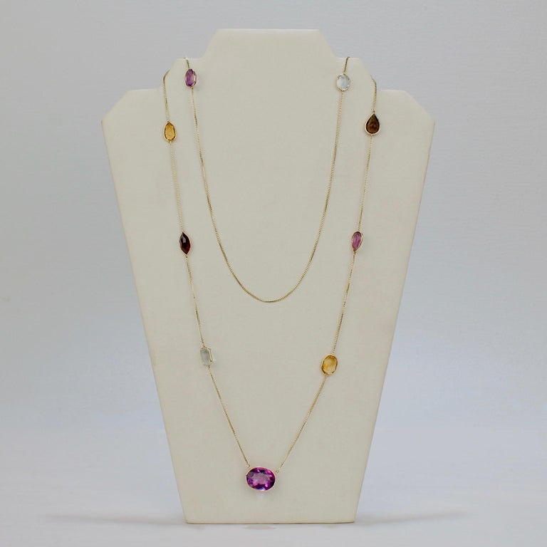 A fine Mid-century rope-length gold and gemstone necklace.  With a box chain in 14k yellow gold supporting bezel-set, pear and oval cut amethyst, topaz, and citrine gemstones.   A great necklace that can be worn at full rope length or elegantly