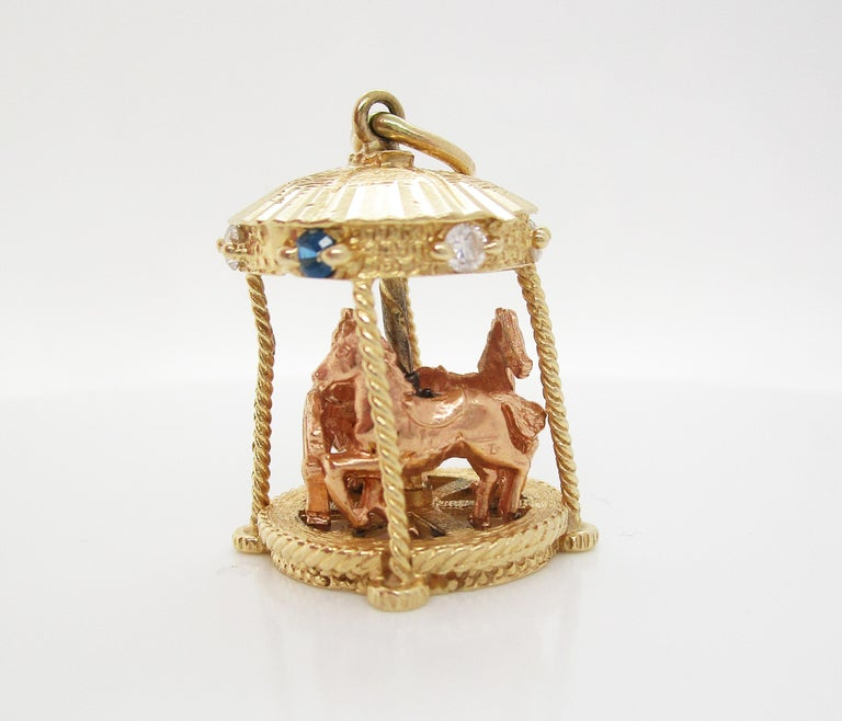 This incredible mid-century pendant is in 14k yellow gold and is an awesome moving carousel design! The carousel is all 14k yellow gold and features three rose gold horses that really move up, down, and around the carousel! The top of the carousel