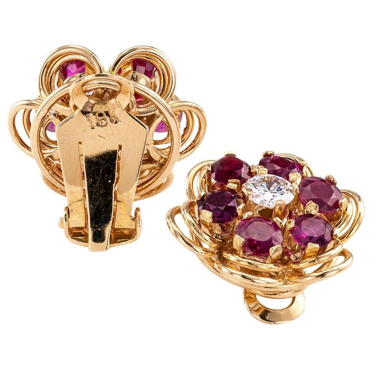 Mid century ruby and diamond gold ear clips circa 1950. The hand fabricated rosette designs centering a pair of round diamonds together weighing approximately 0.70 carat, approximately H - I color and VS - SI clarity, encircled by round rubies