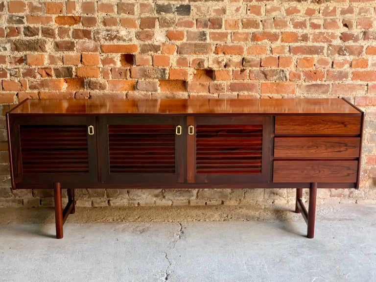 Magnificent midcentury A. H. McIntosh & Co of Kirkcaldy rosewood sideboard credenza, circa 1970s, the rectangular top over three louvered cupboard doors with brass handles and shelves within, three drawers to the right side and raised one four