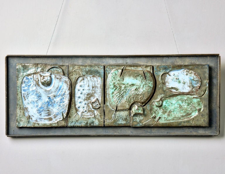 Found in Belgium, this circa 1960s ceramic plaque is glazed in tones of green and blue and mounted upon a dark gray painted wooden frame . The ceramic plaque features four etched abstract cats with some elements rendered in relief. Unsigned -