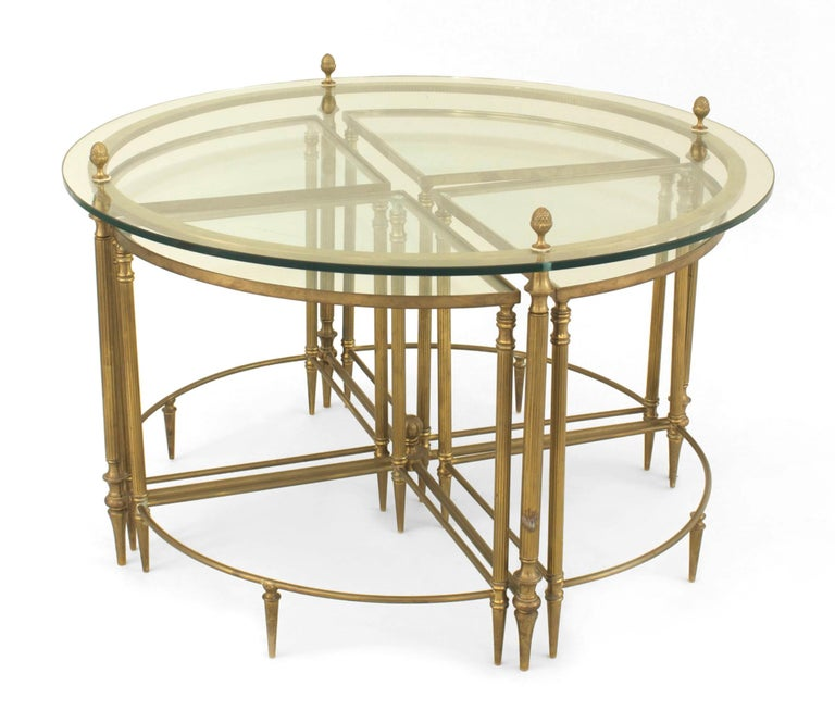 Mid-century American brass round coffee table with a glass top supported by acorn finials and a lower stretcher which fits 4 small wedge shaped glass top tables.