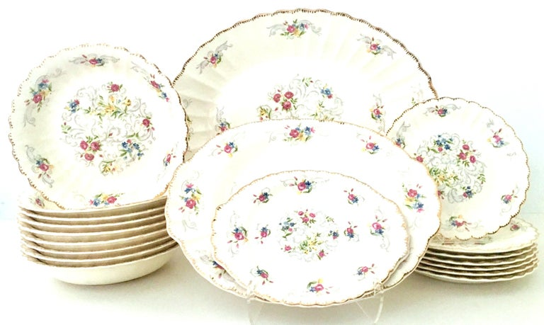 Mid-Century American Limoges set of 19 pieces By, Jennie Lind. Pattern features an off-white ground with hand-painted filigree 22-karat gold edge and a vibrant with muted gray scroll floral pattern. Each piece is signed on the underside, Made In The