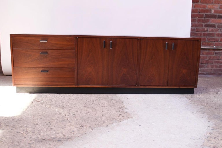 Midcentury American credenza composed of a walnut frame with an ebonized plinth-base and ebonized aluminum pulls with chrome-plated platforms. Features three drawers to the left and two cabinets to the right, each interior space flanked by an