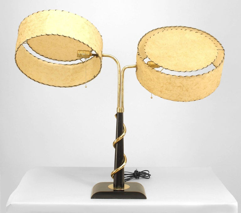 Attributed to the Majestic Lamp Company, a 1950's or 1960's American ebonized and brass student lamp with an adjustable gold decorated drum beneath fiberglass faux parchment shades.