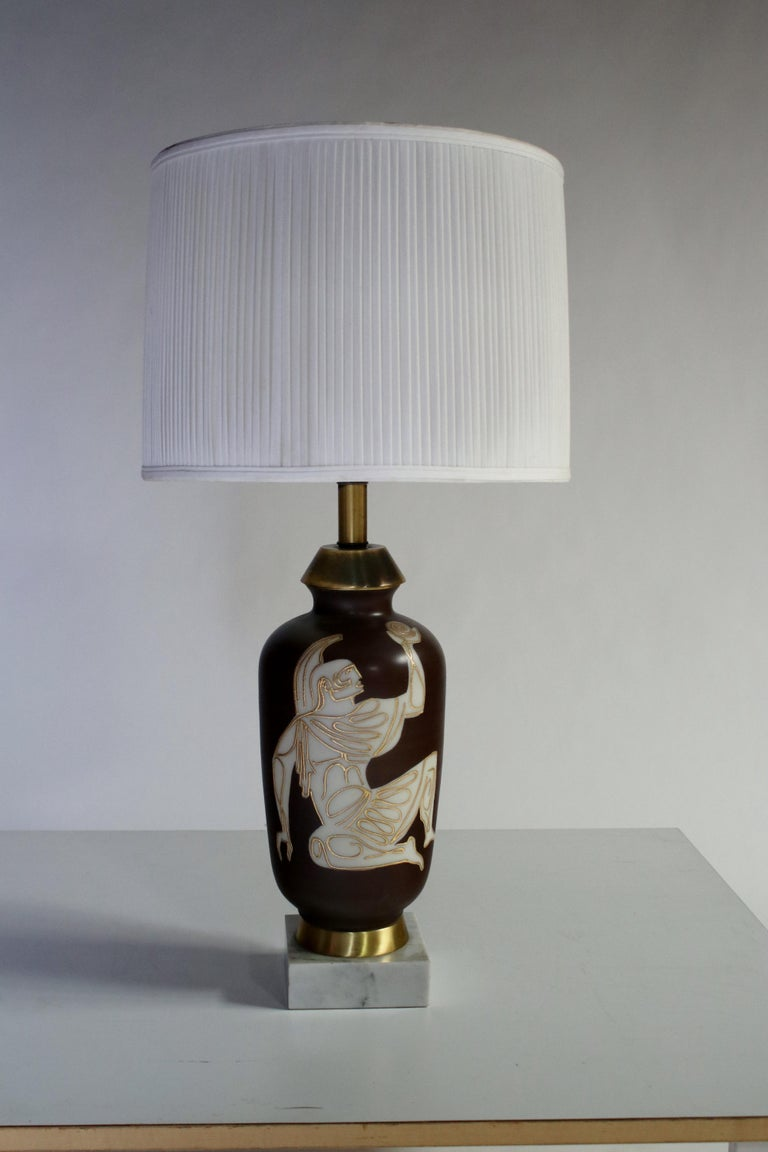 Unique mid-century table lamp depicting a Roman gladiator motif with ancient symbols on a brown glazed urn. Lamp is mounted on a thick marble plinth with brushed brass accents.