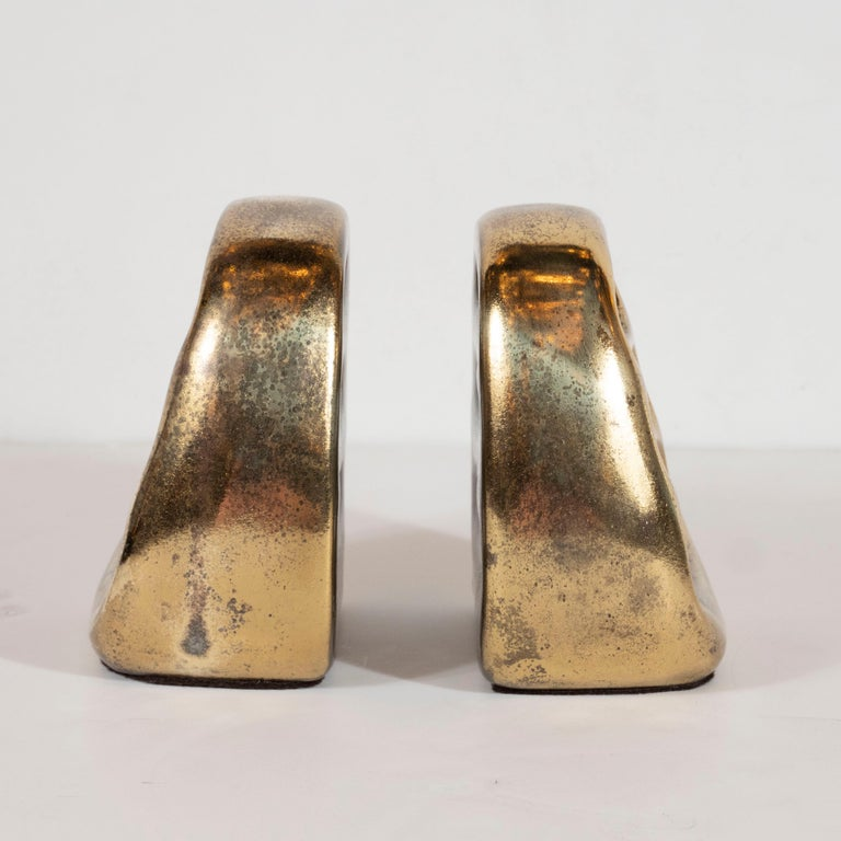 This elegant pair of book ends were realized by the esteemed Ben Seibel for Jenfred-Ware, circa 1950. They feature ovoid forms in glazed ceramic that come to an arched apex above three ovoid cutout- all realized in a lustrous antiqued brass enamel