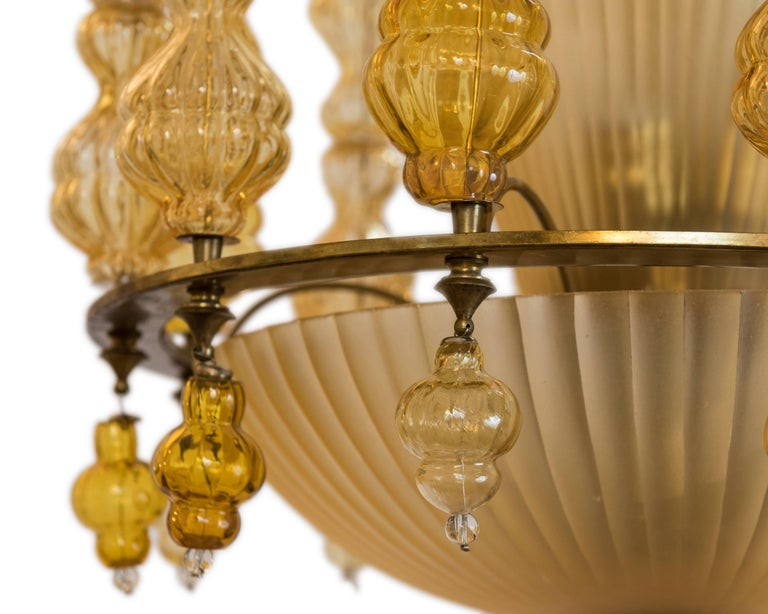 This is an exceptional and amazing amber glass pendant with four illuminated interior beveled deco style bowls in a brass frame with strings of handblown Murano baubles! Truly unique!