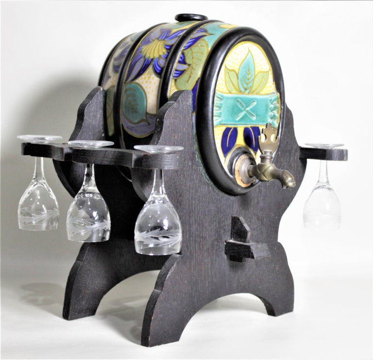 This Mid-Century Modern art pottery keg with glasses and serving Stand is not signed legibly, but is clearly done in the manner and style of Gouda art pottery of Holland. The set consists of the hand painted art pottery keg barrel styled decanter