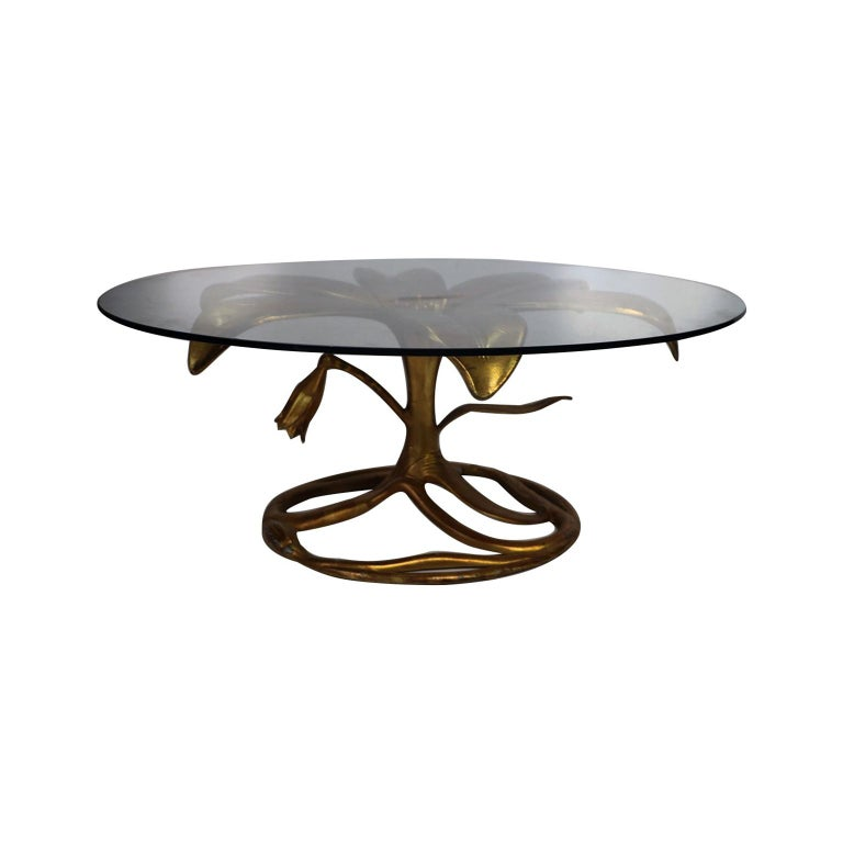 Stunning gilded lily cocktail table with circular glass top by Arthur Court, circa 1970s. This eye-catching conversation piece features a gold cast aluminum base with an open lily bloom supporting a thick glass top above a closed bloom and leaf
