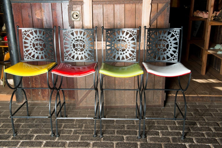 A set of four mid-century Mayan sun face back iron bar stools by Arthur Umanoff for Shaver Howard. Two seats are red and white vinyl. Two seats are yellow and lime green. All are in very nice condition.