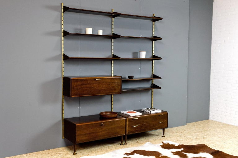 Original modular wall unit executed in polished ash with brass details and uprights, designed by Abraham Patijn during the early 1950s. The trumpet feet, and the rounded shelves and cabinets, show the great craftsmanship of Dutch Mid-Century Modern