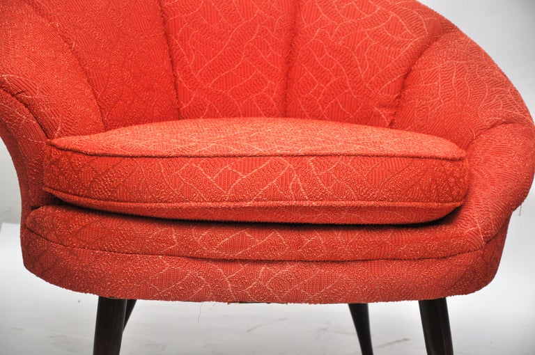 Asymmetrical Hollywood glamor chairs have their original bright orange upholstery. These chairs were in custom made plastic covers that appeared to have always been on them. The upholstery has some fading. They would benefit from being reupholstered