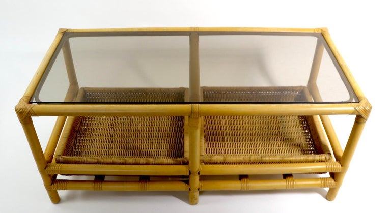 Good quality mid century coffee table with a bamboo frame, Formica top, removable two wicker trays, and a  tinted plate glass top. Well-crafted and in good original condition, clean and ready to use. Manufacture attributed to Ficks Reed,
