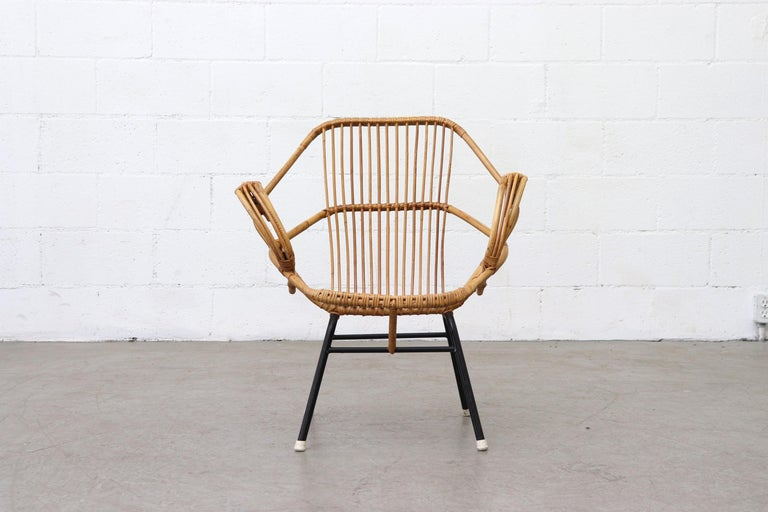Geometric hexagon shaped bamboo lounge chair with arms, black enameled metal frame and white rubber feet. In original condition with some signs of wear consistent with its age and use. Other bamboo chairs and sofas available, listed separately.