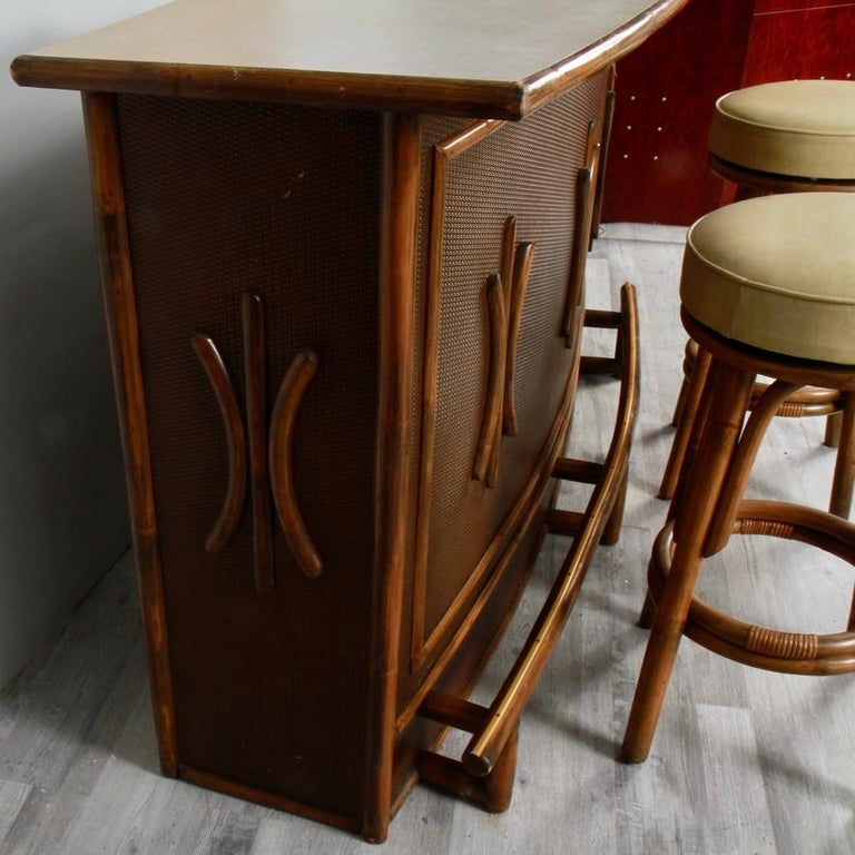 A clean survivor from a 70s basement, ready to move on up and entertain in a more modern family room. Sturdy and well made from thick hardwood with a bamboo veneer, there's plenty of room to store bottles and barware. Its top is vintage Formica. The