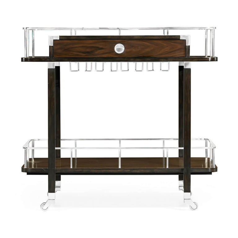 Mid-Century Modern style rosewood rolling bar cart in the Campaign form style with silvered brass galleries, glass top with hanging supports, and drawer.  Dimensions: 35.5