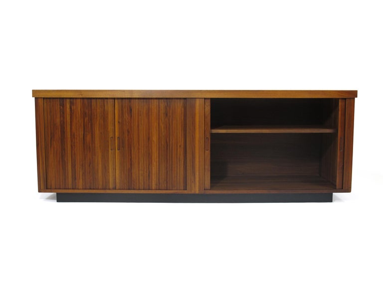 Midcentury Barzilay walnut credenza with pair of tambour doors with inset pulls which open to reveal an interior with adjustable shelves. Raised on a plinth base with black Formica top surface. Very good original condition.