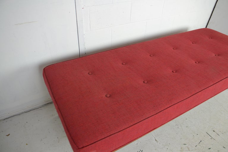 A large mid-century upholstered teak-wood bench.
