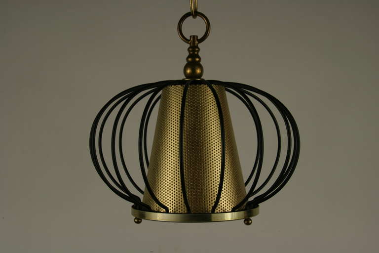 Lightolier  brass perforated cone center ending with a frosted glass lenses set in a black metal frame. One Edison based bulb 75 watt. Priced individually. Two available.