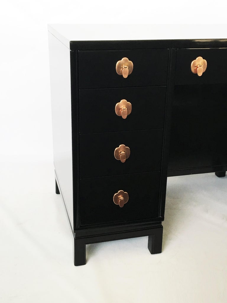 Asian style eight-drawer desk manufactured by Landstrom Furniture of Rockford, Illinois. Perfectly proportioned desk in black lacquer finish, chinoiserie styling with aged copper drop disc pulls and trefoil escutcheons on platform style four leg