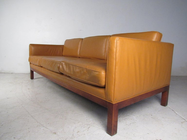 This impressive vintage modern sofa boasts six overstuffed removable cushions ensuring maximum comfort in any seating arrangement. A sleek design covered in tan leather that sits on a sturdy walnut base. This stunning midcentury sofa adds style and