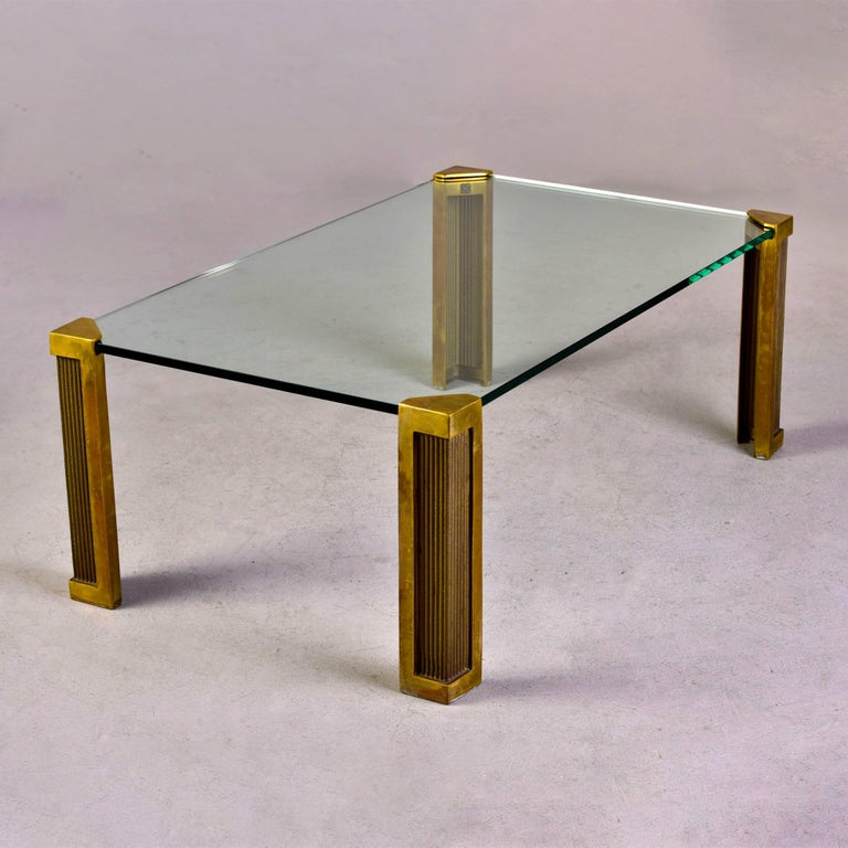 Circa 1970s coffee / cocktail table created by German designer Peter Ghyczy of Germany features a thick glass top with each corner fitted / inset to heavy cast brass legs with decorative surface texture and detail.