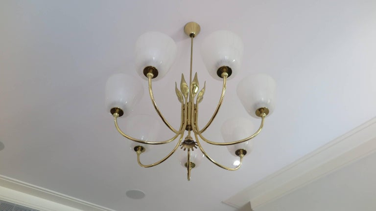 Scandinavian Mid-Century Modern chandelier made by Boréns Aktiebolag, Borås. Having seven arms made of polished lacquered brass holding white frosted glass shades with linear etching details. The brass arms turning in and upward to the centre stem,