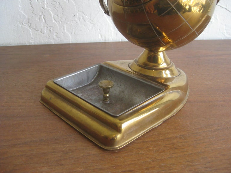 Brass figural globe cigarette holder and ashtray caddy, circa 1950s. Would make a great office desk accessory. Wonderful midcentury design. Nice patina and could polish up if desired. Opens as it should to store cigarettes inside the globe. In very