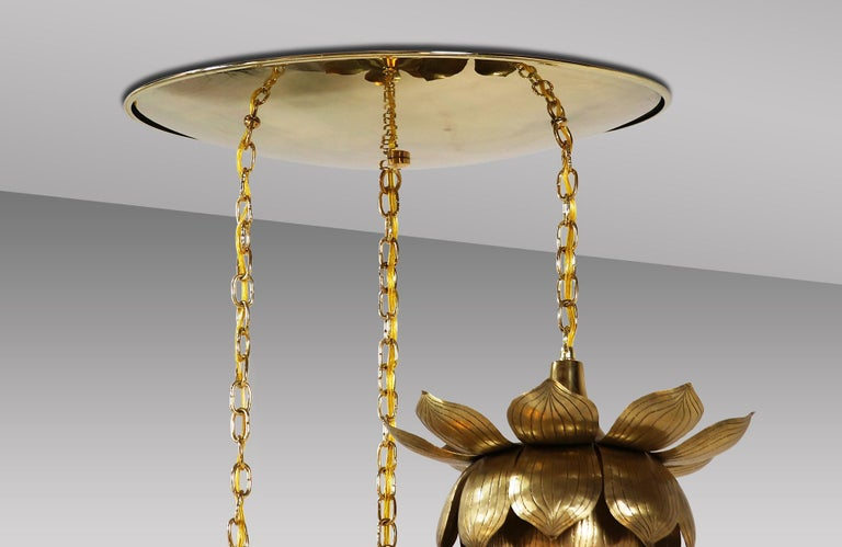 Sculptural lotus chandelier designed and manufactured by Feldman Lighting Co. in the United States circa 1960s. This stunning flower pendant features three polished brass lotus flowers with a delicate patina hanging from chains attached to a
