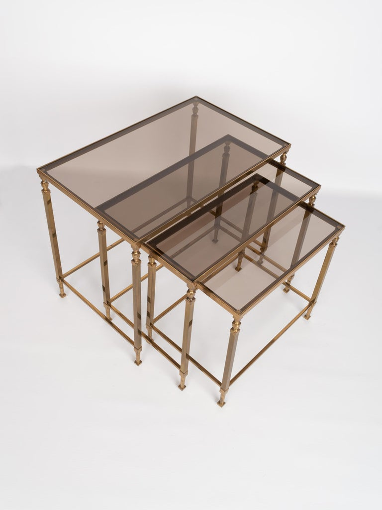 Midcentury brass and smoked glass nesting tables by Maison Baguès, France, circa 1960. Presented in very good vintage condition commensurate of age.  Dimensions: H 44 x W 52.5 x D 32.5 cm H 40 x W 45.5 x D 29.5 cm H 36 x W 38.5 x D 26.5 cm