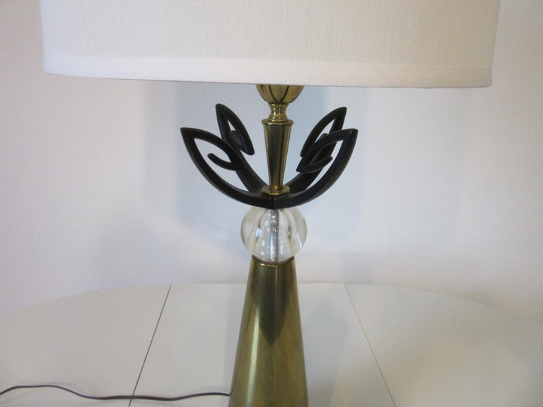 A well crafted heavy brass and satin black metal table lamp with decorative metal work and hand blown clear glass ball. Manufactured by the Aurora Lamp company in the manner of Rembrandt lighting.