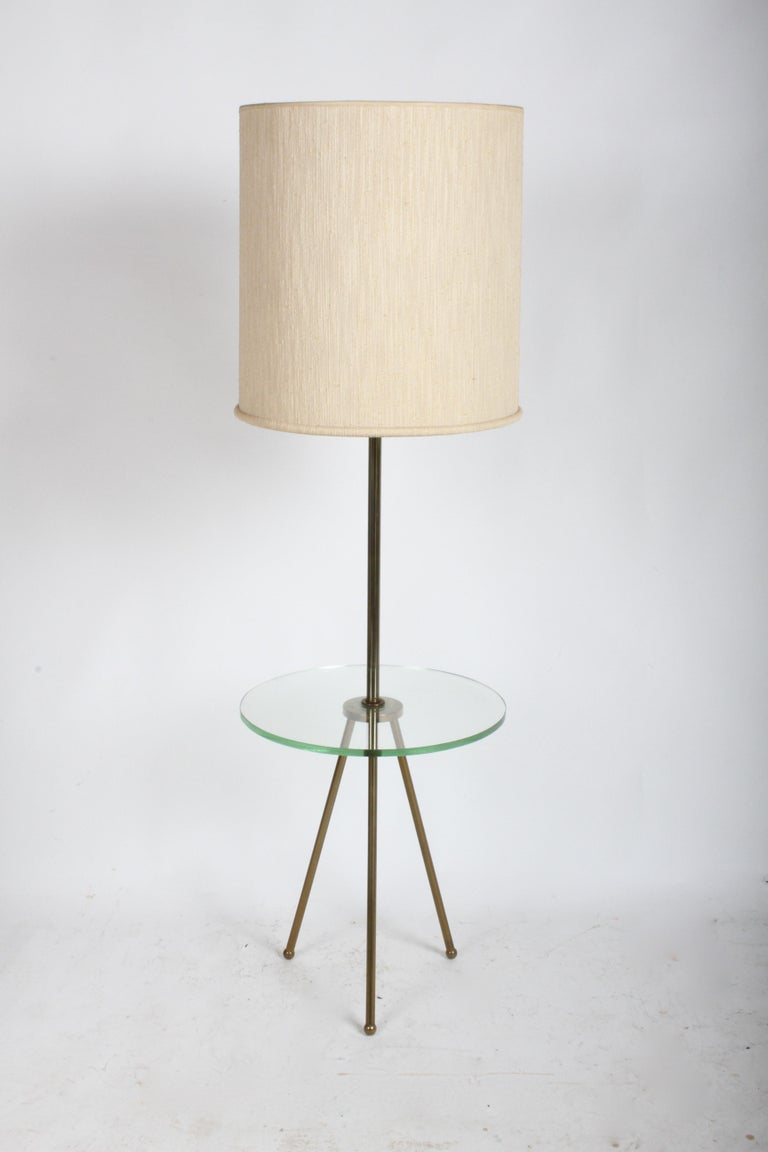 Mid-Century Modern floor lamp having brass tripod legs with round glass shelf, in the style of Fontana Arte. Unknown designer, but also has the look of Italian modern designers. Shade not included, shade specs shown are 19