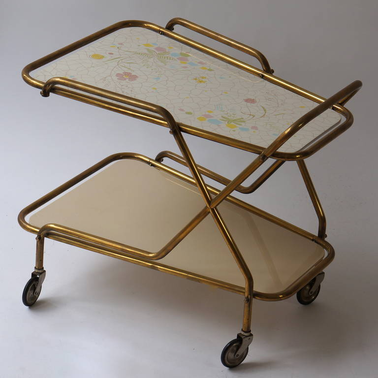 Italian brass serving table or liquor trolley. Elegant liquor trolley or serving table with brass frame which supports the removable hand painted tray with beautiful flowers. Quality and craftsmanship. Measures; Height 63 cm. Width 72 cm. depth