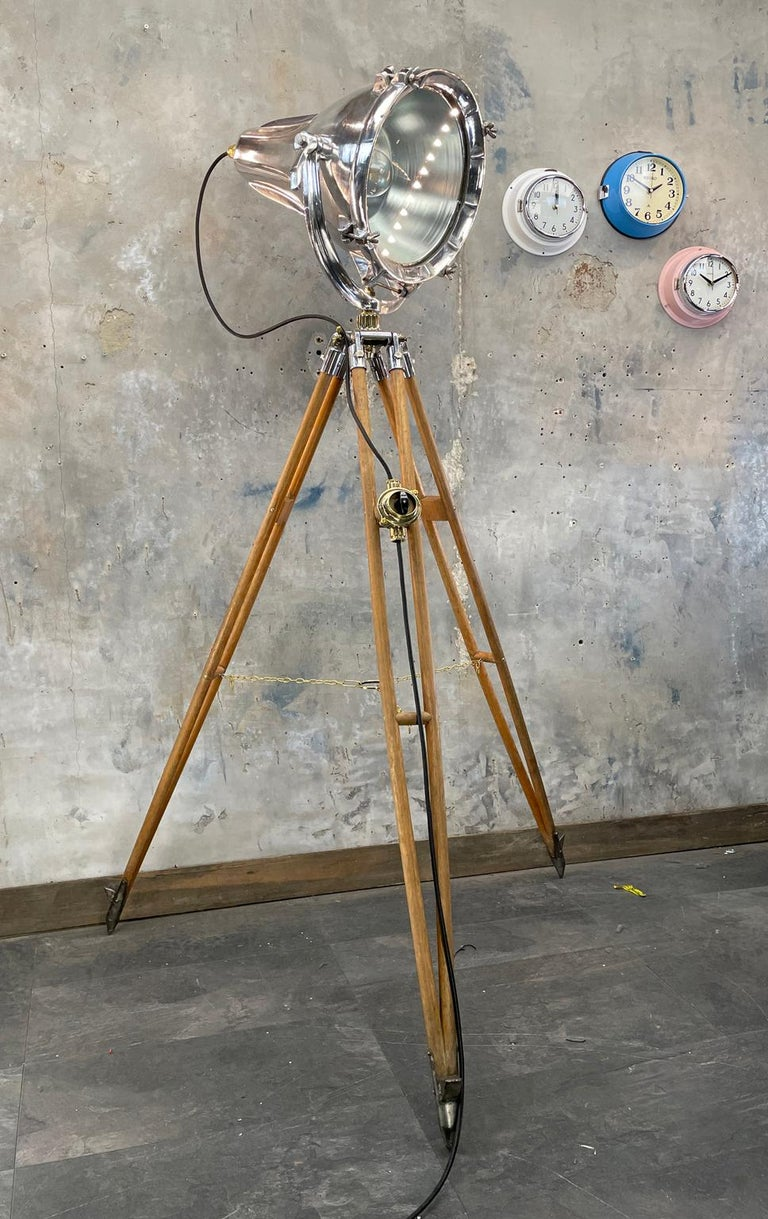 A tall floor standing tripod lamp comprising of a British made cast aluminium cargo light and E.R Watts & Sons of London Surveyors Tripod dating from the 1940s.  The lamp is reclaimed from a supertanker and would of illuminated large areas on