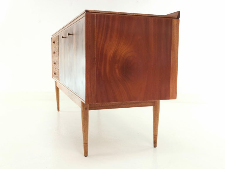 Offered a sort after Archie Shine 'Hanover' compact sideboard, this rarely available compact design with four drawers with recessed brass trumpet-shaped handles inset into the Rosewood. Two doors with matching handles sit over a storage area with